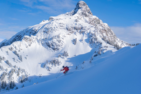 Skier on powder slope with iconic mountain in background